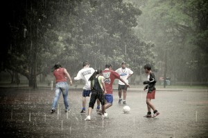 """Teenagers playing soccer in the rain"", de Marlon Dias"