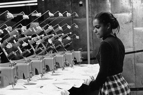 A young African American woman watches at least seven sewing machines working simultaneously, de Kheel Center