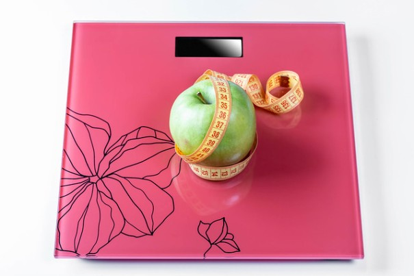 """Apple wrapped with measuring tape on the scales as a symbol of a healthy diet"", de Marco Verch, al Flickr"